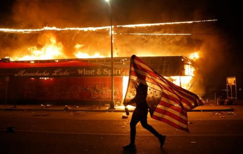 A protester runs in front of a burning building in Minneapolis waving an upside down flag, a symbol of emergency or danger.