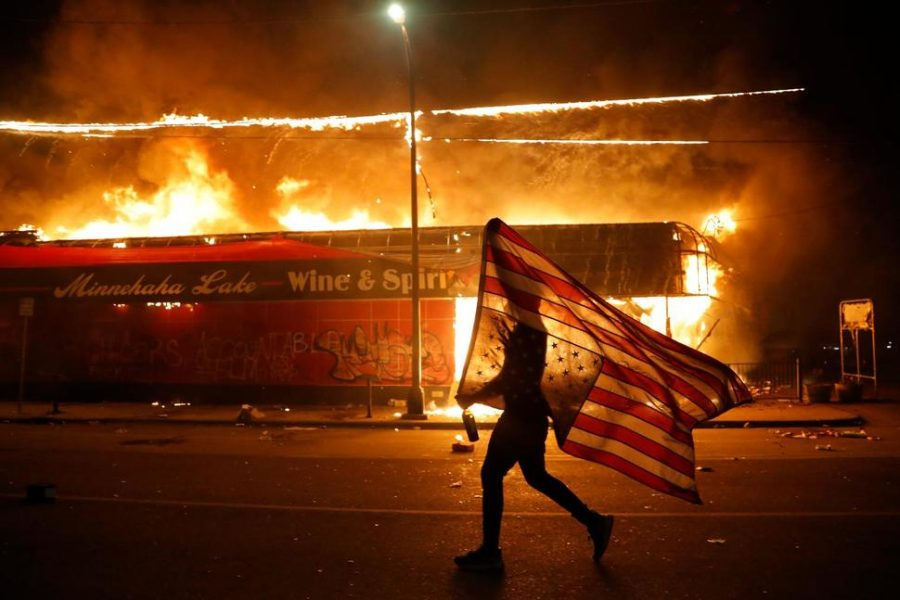 A+protester+runs+in+front+of+a+burning+building+in+Minneapolis+waving+an+upside+down+flag%2C+a+symbol+of+emergency+or+danger.+