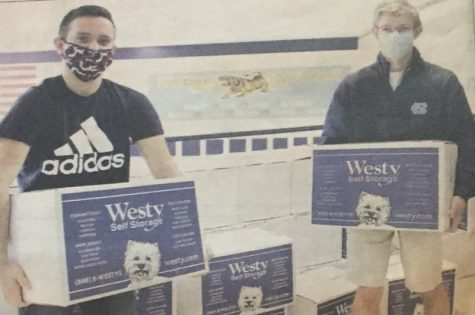 Feed 200 senior leader Ryan Inzerillo and National Honor Society Co-President Griffin Crafa hold Feed 200 boxes. (Credit: The Observer / David Ambro — modified by Griffin Crafa)